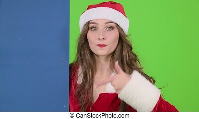 Santa woman peeps showing a finger on a blue board advertising billboard. Green screen. Close up