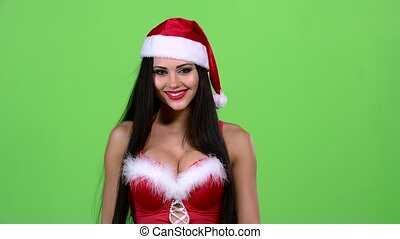 Santa woman walking by foot and sends and air kiss. Green screen