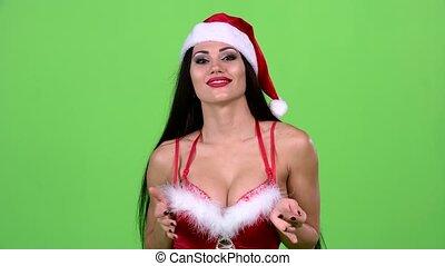 Santa woman walking by foot and sends and air kiss. Green...