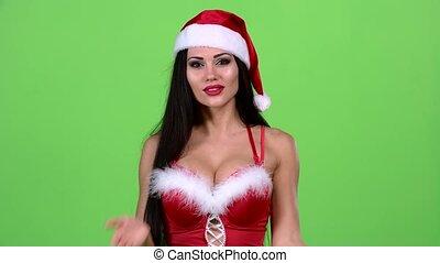 Santa woman walking by foot and sends and air kiss. Green screen