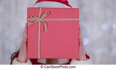 Santas assistant covered her face with a gift and looked out for him. Bokeh background. Close up . Slow motion