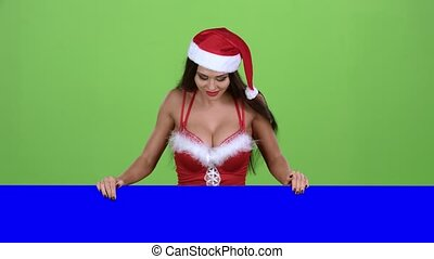 Santas assistant looks out of the blue board and shows a thumbs down. Green screen