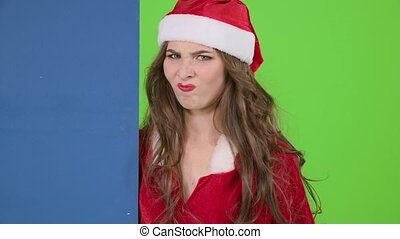 Santas assistant looks out of the blue board and shows a...