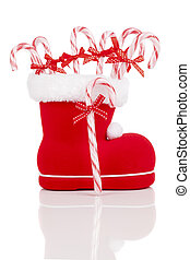 Santa's boot with candy canes on white background