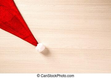 Santa's hat on wooden planks. Christmas background.