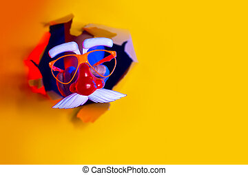 Santa's mask in hand protrudes from a hole in yellow background, illuminated by neon light