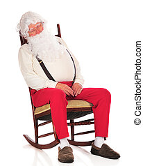 Santa snoozing in his rocker after a hard day in the toy shop. Isolated on white.