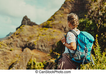 Santo Antao island, Cabo Verde. Woman tourist with backpack enjoy the view during the hike in arid terrain