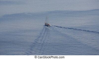 Santorini, Greece. A vintage sailing ship sails through the...
