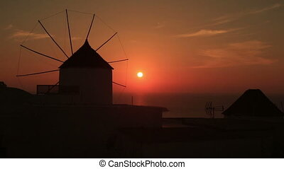 Santorini with famous windmill in Greece, Oia village on beautiful red sunset