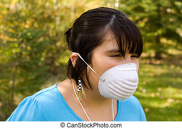 SARS - A young girl wearing a mask to protect herself from...