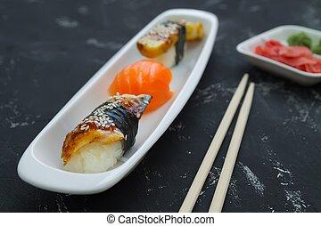 sashimi on a white plate of vassabi ginger