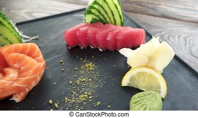 Sashimi plate on the table. Raw fish, ginger and cucumber.