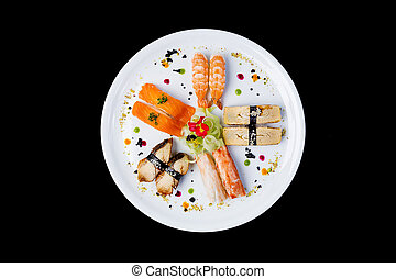Sashimi set on a white round plate, decorated with small flowers, Japanese food. Top view. Isolated on a black background