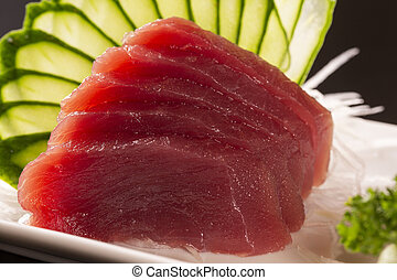 sashimi with tuna in a white plate. On a black background.