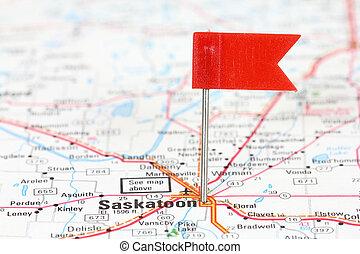 Saskatoon in Saskatchewan, Canada. Red flag pin on an old map showing travel destination.