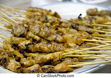 Satay; meat on thin bamboo sticks barbecued on a coal flame