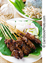 Satay or sate, skewered and grilled meat, served with peanut...