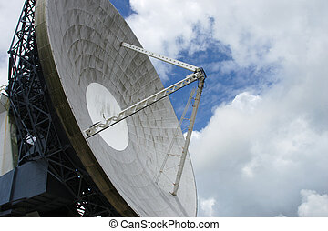 satellite dish against blue patch in cloudy sky
