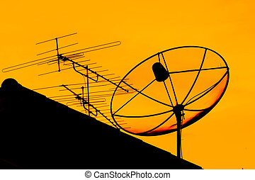 Satellite dish and home TV antenna in the evening -...