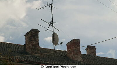 Satellite dish and tv antenna mounted on roof of an old house