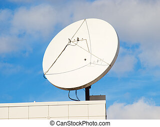 Satellite dish on the modern building roof corner with blue sky in the background.