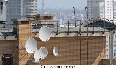Satellite dishes on the house roof - Brick house rooftop...