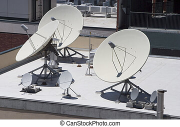 Satellite dishes point skyward on top of a building.