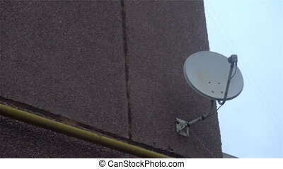 Satellite receiver dish on the wall with a cloudy sky and cloud behind