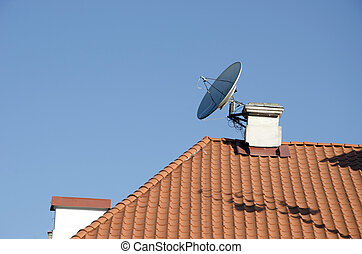 Satellite television antenna attached to chimney on red...