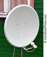 Satellite TV antenna on the wall of a wooden house