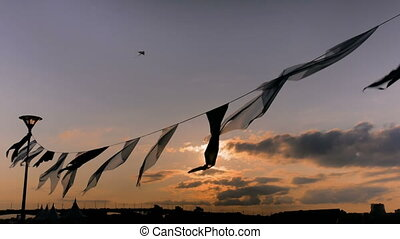 Satin flags waving in the wind at sunset