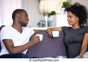 Satisfied African American couple talking, drinking coffee at home