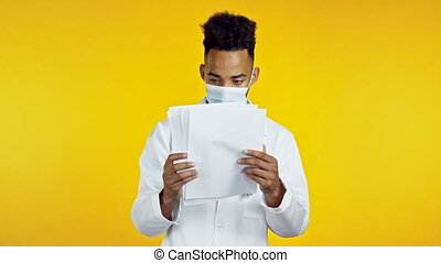 Satisfied african doc man in professional medical coat and mask holding files papers isolated on yellow background. He nods his head approvingly to diagnosis. Doctor with stethoscope