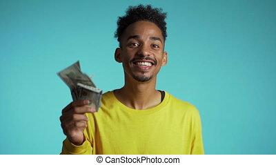 Satisfied african man showing money - U.S. currency dollars ...