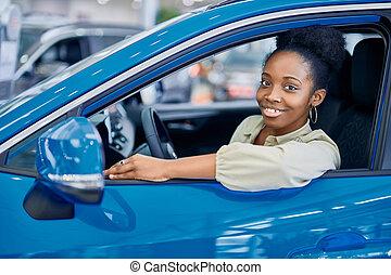 satisfied african woman behind the wheel
