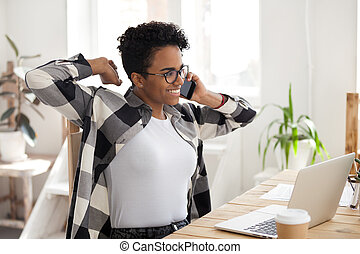 Satisfied African woman talk by phone, happy finish to work