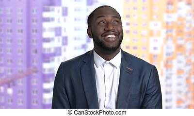 Satisfied afro-american businessman on blurred background....