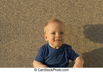 Satisfied baby boy Against the background of a concrete wall. Infant kid with unusual shadows on his face