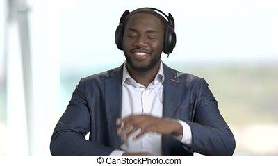 Satisfied businessman listening to music in headphones....