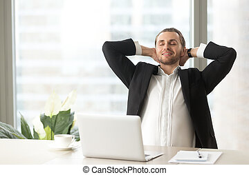 Satisfied businessman relaxing at workplace