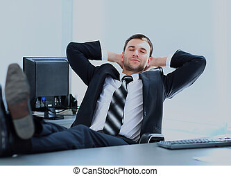 Satisfied businessman relaxing in his office.