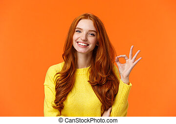 Satisfied consumer recommends product. Cute cheerful feminine redhead woman with pretty smile, showing okay gesture, like, agree or approve something, giving positive feedback, orange background