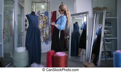 Skillful seamstress looking at tailored dress on mannequin with satisfaction. Pleased female fashion designer satisfied with result of her work on mannequin
