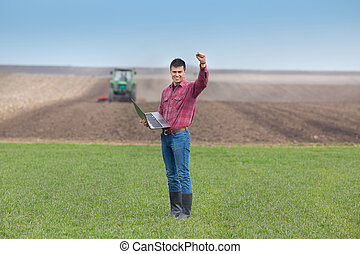 Satisfied landowner with laptop holding fist up in the air on farmland, tractor plowing in background