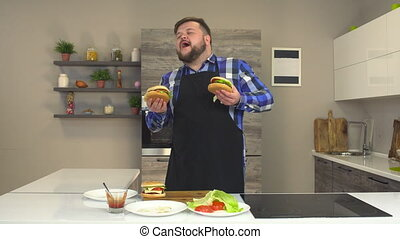 Satisfied fat man with a beard and apron dancing and smiling...
