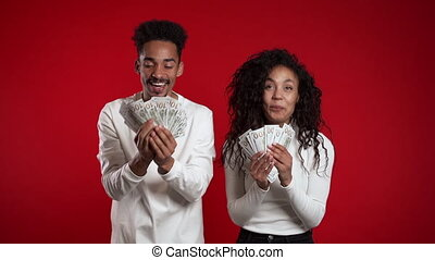 Satisfied happy excited african couple showing money - U.S. ...