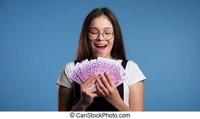 Satisfied happy excited asian girl showing money - euro ...
