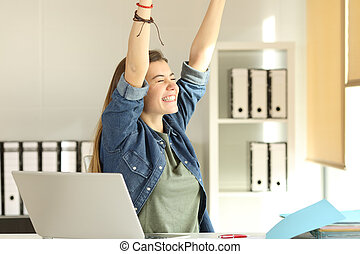 Satisfied intern raising arms at office
