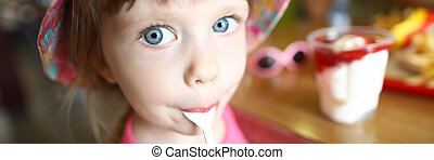 Satisfied little child licks spoon with ice